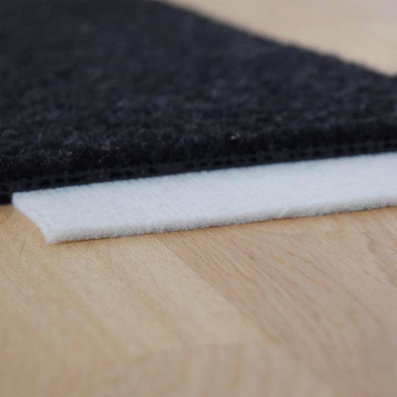 Teppichunterlage weiß unter schwarzem Teppich auf Parkett